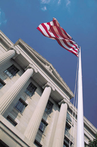 courthouse shot from a low angle with american flag waving in a moderate breeze